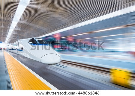 high speed train in modern railway station with motion blur - stock photo