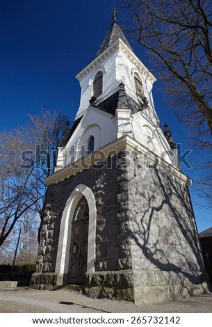 High steeple of a church on a sunny spring day. Old religious building with very strong perspective and blue sky on the background. - stock photo