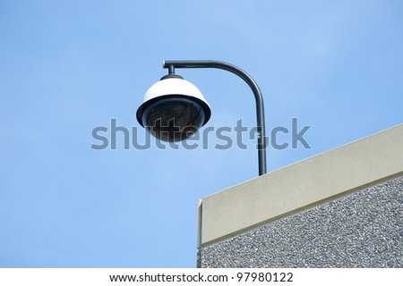 High tech overhead security camera on commercial building - stock photo