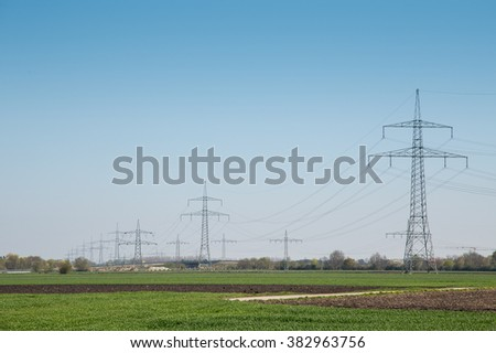 High-tension power line on meadow