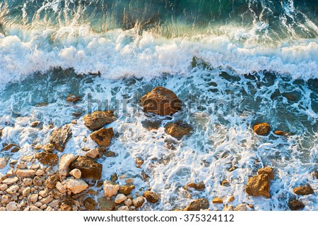 High tide on a rocky beach at sunset - stock photo