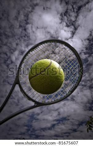High up yellow tennis ball and racket on clouds background. - stock photo