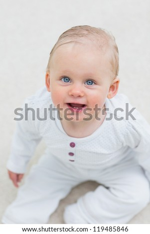 High view of a baby sitting in living room - stock photo