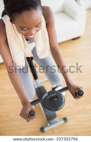 High view of a black woman sitting on an exercise bike in a living room