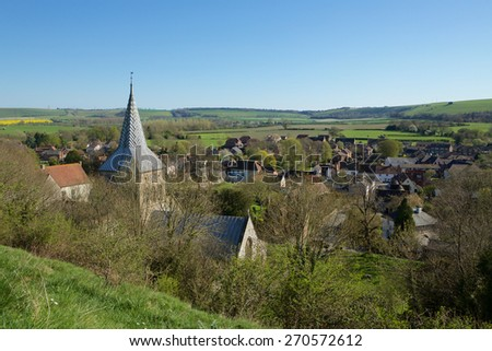 High view of a village in the Meon valley in Hampshire England. Taken from a high vantage point with focus on the village church steeple. - stock photo