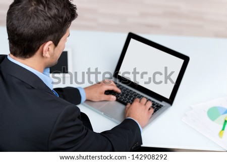 High view rear view of young businessman using laptop at desk in office - stock photo