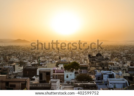 High view showing part of the Udaipur skyline at sunrise. Lots of buildings can be seen and hills and the sun can be seen in the distant. - stock photo