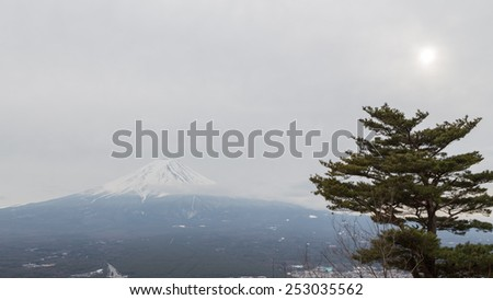 high volcano Mount Fuji in the suburbs of Tokyo, pine and the sun peeps through the clouds in winter, Japan - stock photo