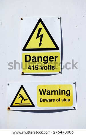 High voltage danger warning sign for 415 volts of electricity with an additional warning to beware of a step below mounted on a white wall - stock photo