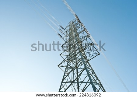high voltage electric power lines on pylons in blue sky. - stock photo