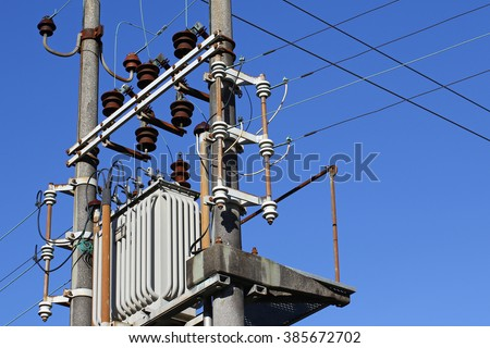 High voltage electrical transformer high on concrete poles - stock photo