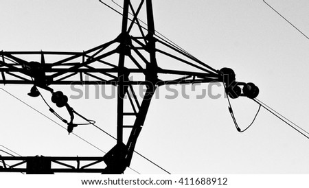 High voltage electrical transmission towers electricity pylons and power lines black silhouettes close up, black and white image - stock photo