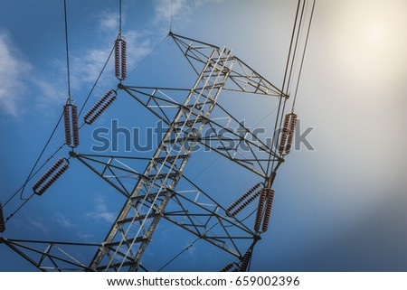 high voltage electricity post on blue sky background and sun flare