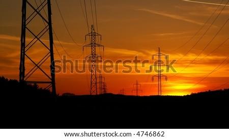 High voltage electricity pylon over sunset - stock photo
