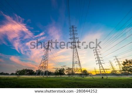 High voltage electricity pylon system on sunrise background - stock photo