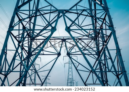 high voltage electricity transmission pylon silhouetted against blue sky   - stock photo