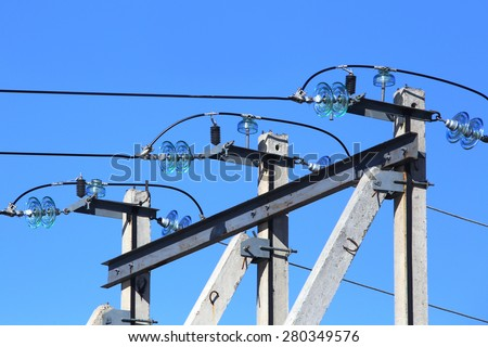 High-voltage glass insulator on power line against the blue sky - stock photo