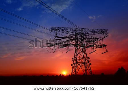 High voltage isolation tower in the fields under the setting sun