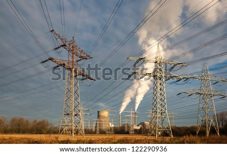 High voltage lines and power pylons in the foreground and in the background the power station with smoking chimneys and a colling tower. - stock photo