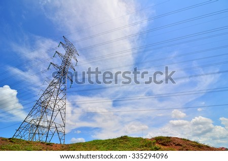 High voltage lines and power pylons tower on a sunny day with clouds in the blue sky - stock photo
