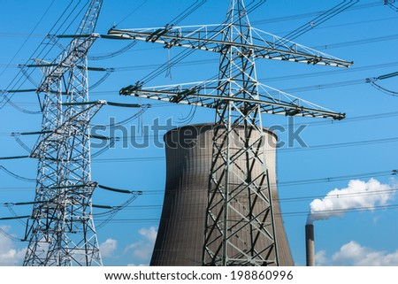 High voltage lines, power pylons, a chimney with white smoke and a concrete cooling tower of a power station together against a bright blue sky. - stock photo