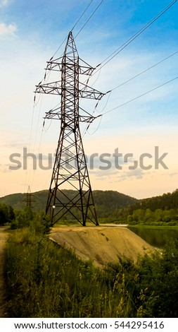 high-voltage metal pillar stands on the banks of the great river. The mountains and forest