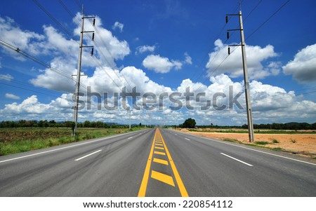 High voltage poles and yellow line on the road. - stock photo