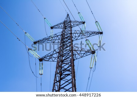 High voltage post. Electricity pylon against blue sky - stock photo