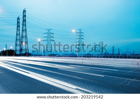 high voltage post.High-voltage tower sky background,besides the highway - stock photo