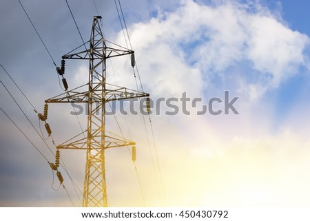 High voltage post on blue sky with clouds background. Sunlight