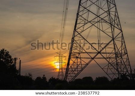 High voltage post on sunset - stock photo