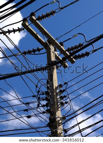 High voltage post or power transmission line tower on blue sky - stock photo