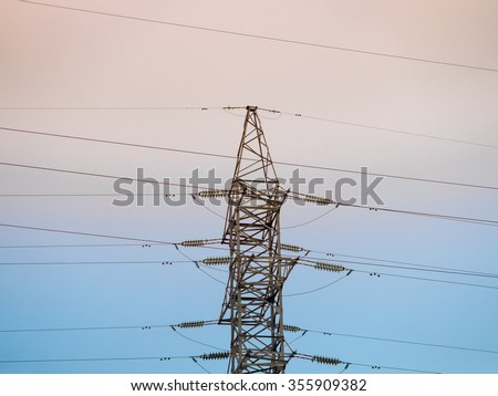 High voltage post or transmission tower and clear sunset sky as background - stock photo