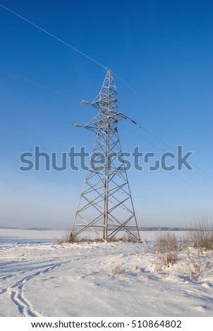High-voltage power line in the winter against the blue sky
