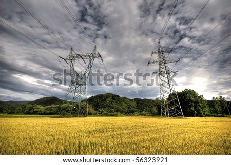 High voltage power lines above wheat field just before storm - stock photo