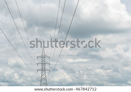 High voltage power lines and pylon on dark cloud background