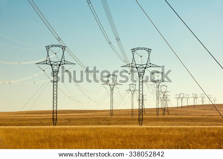 High voltage power lines and transmission towers (electric pylons) wind their way across the grassy plains on a sunny day. - stock photo