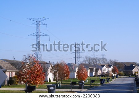 High voltage power lines crossing behind a suburban setting