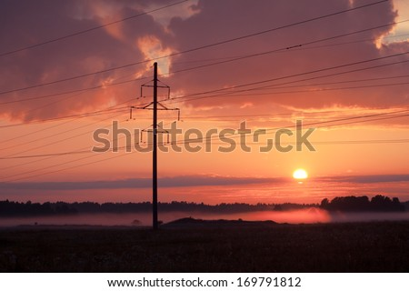 High voltage power lines, fog and sunset - stock photo