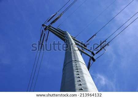 High Voltage Power Lines intersect at a large metal Utility pole in Maine against a blue sky. - stock photo