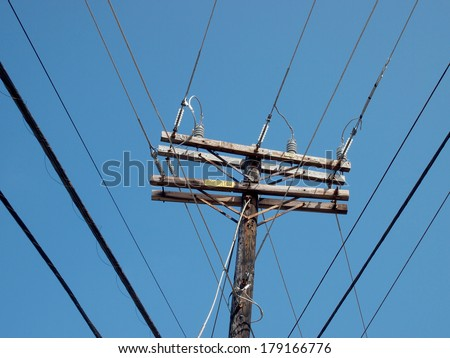 High Voltage Power Lines intersect at a wooden Utility pole on Oahu, Hawaii. - stock photo