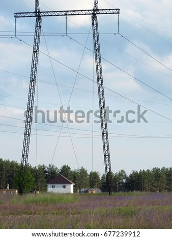 High voltage power lines run along the summer agricultural landscape