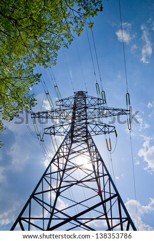 high voltage power lines with blue sky, sun and tree - stock photo