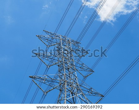 High-voltage power pole soaring into blue sky - stock photo