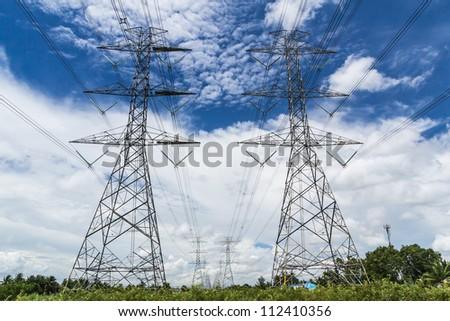 high voltage power pylon against blue sky - stock photo