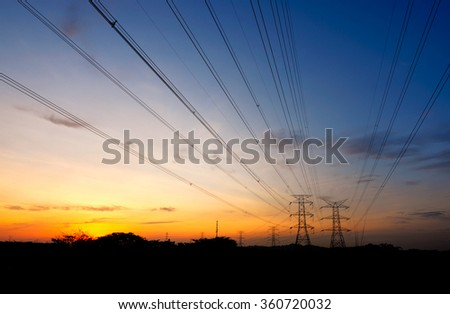 High voltage power tower and power lines on blue hour and sunset