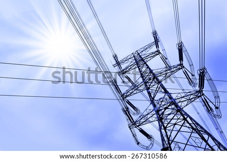 High voltage power tower pylon and line cables, sun and blue sky background - stock photo