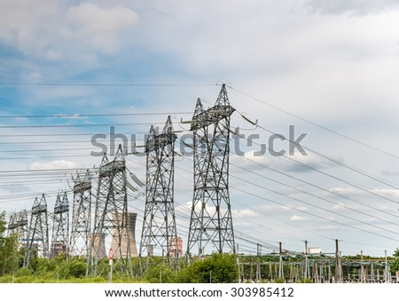 High-voltage power transmission towers in clear blue sky background. - stock photo