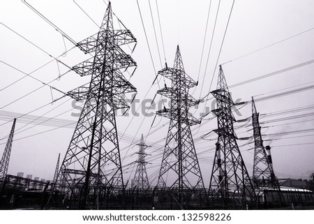 High-voltage power transmission towers in polluted gray sky background. - stock photo