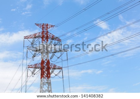 High voltage powerline and pylon against bright blue sky with white clouds - stock photo